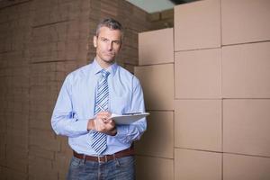 Portrait de gestionnaire avec presse-papiers dans l'entrepôt photo