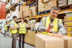 ouvrier d'entrepôt scellant des boîtes en carton pour l'expédition photo