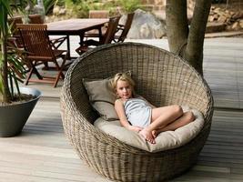 fille assise dans une chaise en osier, portrait