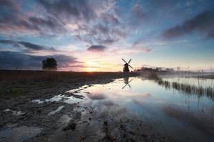 Charmant lever de soleil derrière le moulin à vent hollandais photo