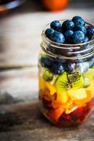 Salade de fruits colorés dans un pot sur fond de bois rustique photo