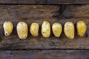 Les jeunes pommes de terre d'affilée sur un bois rustique foncé
