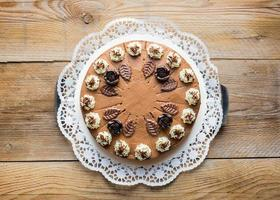 Tarte à la crème au chocolat sur le dessus du gâteau en bois rustique photo