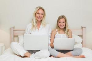 heureuse mère et fille à l'aide d'ordinateurs portables au lit photo