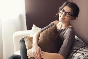 Femme portant des lunettes de mode assis sur un canapé à la maison photo