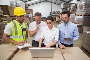 gérants d & # 39; entrepôt et travailleur regardant un ordinateur portable photo