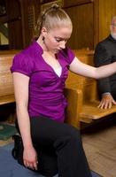 Jeune femme blanche génuflexion à côté de banc d'église photo