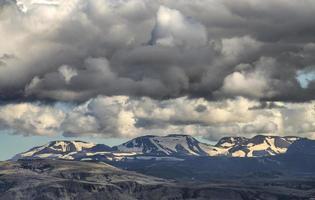 montagne couverte de neige sous un ciel blanc et gris