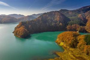 Montagne à côté du lac bleu sous le ciel bleu pendant la saison d'automne