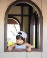 petite fille debout près de la fenêtre photo