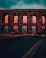 Feux de circulation contre un aqueduc âgé au coucher du soleil photo