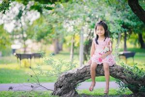 fille asiatique avec une poupée assise dans le parc