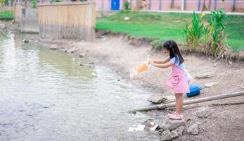 Une petite fille nourrir les poissons à l'étang dans un parc public