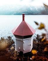 structure de phare blanc et rouge près du plan d'eau
