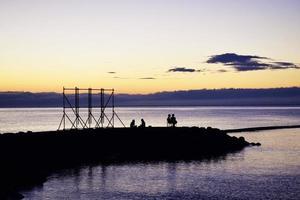 silhouette de personnes assises près d'un plan d'eau photo