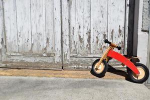 Parc à vélos orange pour tout-petits à côté de la porte