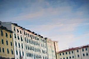 Réflexion d'un bâtiment blanc dans une flaque de rue pendant la journée