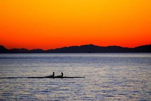 silhouette de deux personnes sur des barques au coucher du soleil photo
