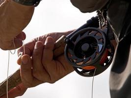 pêcheur à la mouche tient la ligne de pêche photo