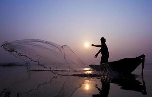 les pêcheurs attrapent des poissons avec un filet moulé.
