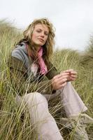 Portrait de jeune femme assise dans l'herbe photo