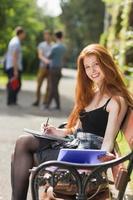 jolie étudiante étudie à l'extérieur sur le campus photo