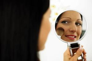 femme utilisant un pinceau de maquillage photo