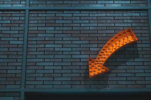 flèche orange sur le mur de briques