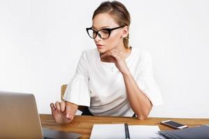Femme réfléchie travaille sur un ordinateur portable au bureau sur fond blanc