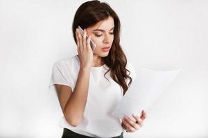 femme habillée en style bureau parle au téléphone de la paperasse