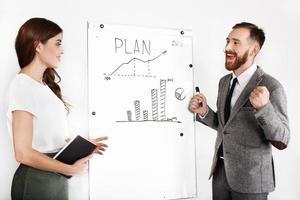 joyeux homme et femme discutent graphique sur tableau blanc