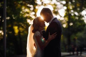 soleil d'été derrière un beau couple de mariage