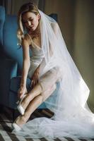 belle mariée dans un voile est assise sur une chaise et fixe ses chaussures de mariage