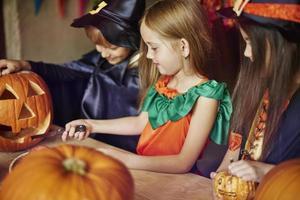 concentrer les enfants à sculpter des formes sur la citrouille photo