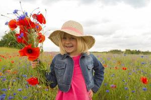heureuse petite fille avec un bouquet de fleurs sauvages.
