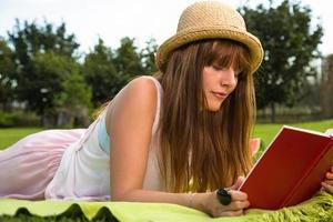 Atractive jeune livre de lecture féminin dans le parc