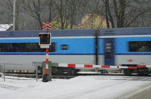 Passage à niveau en hiver avec train dans une tempête de neige