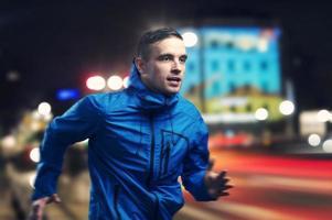 un homme en veste bleue qui court le soir