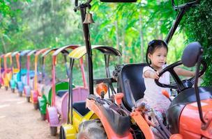 petite fille imitant de conduire un train miniature