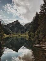 lac entouré de montagnes et d'arbres pendant la journée