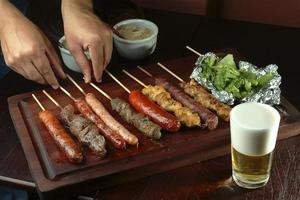 viande barbecue, poulet linguiçae servi sur un bâton photo