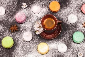 macarons, guimauve et café sur fond noir photo