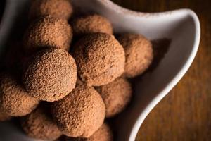 Truffes au chocolat dans un bol sur une table en bois foncé photo