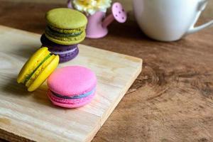 Macarons colorés et une tasse de café sur la table en bois photo