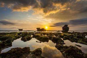 beau coucher de soleil avec rocher moussu vert