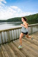 Woman jogging sur pont piétonnier en bois sur le lac Johnson, nc photo