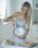 Femme mélangeant la pâte à biscuits dans la cuisine au comptoir photo