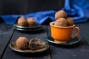 Bonbons aux dattes, chocolat et noix de coco sur fond sombre photo