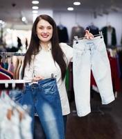 fille choisissant un jean au magasin photo
