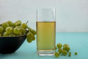 Vue latérale du jus de raisin blanc et des baies sur la surface bleue photo